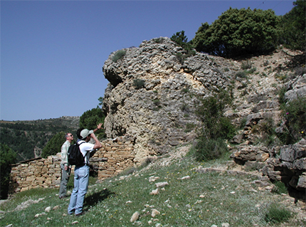 scientists standing near a rock formation